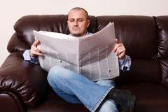 Homem novo com jornal fotos de stock royalty free