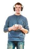 Homem novo com música de escuta dos auscultadores fotografia de stock royalty free