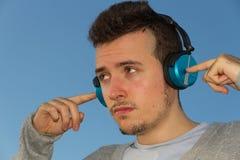 Homem novo com música dos fones de ouvido Fotografia de Stock