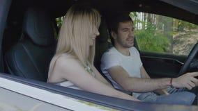 Homem novo com a moça que usa o painel sensorial dentro do automóvel moderno filme
