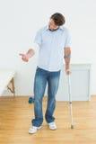Homem novo com muleta e mão enfaixada Imagem de Stock