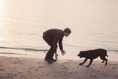 homem novo com o cão na praia Fotos de Stock Royalty Free