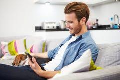 Homem novo com o cão que senta-se em Sofa Using Digital Tablet Imagens de Stock Royalty Free