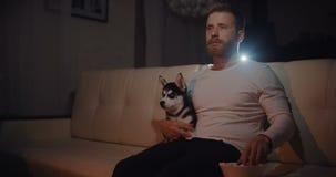 Homem novo com o cão que senta-se em um sofá, em um drama de observação na tevê em casa no grito da sala de visitas e do começo filme