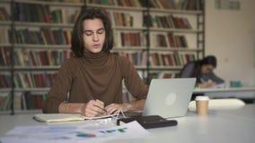 Homem novo com o cabelo longo que faz anotações no caderno que senta-se na biblioteca video estoque