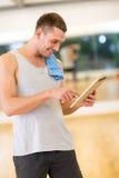 Homem novo com o computador e a toalha do PC da tabuleta no gym Foto de Stock