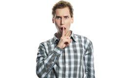 Homem novo com o dedo perto de sua boca sobre o branco Imagem de Stock