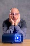 Homem novo com o filme aborrecido do relógio do projektor Fotos de Stock Royalty Free
