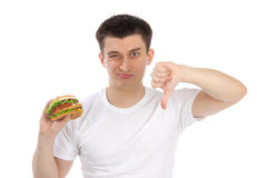 Homem novo com o hamburguer insalubre do fast food saboroso Fotos de Stock Royalty Free