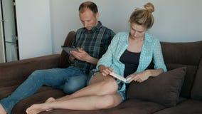 Homem novo com o livro de leitura da tabuleta e da mulher que senta-se no sofá dentro filme