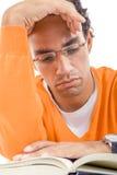 Homem novo com o livro de leitura dos vidros na camiseta Foto de Stock