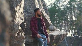 Homem novo com o machado à disposição que senta-se no snone enorme da montanha na borda de um penhasco e que aponta seu dedo Brut filme