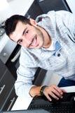 Homem novo com o portátil na cozinha imagem de stock royalty free