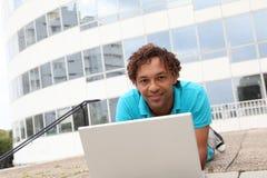 Homem novo com o portátil na frente do edifício imagem de stock royalty free