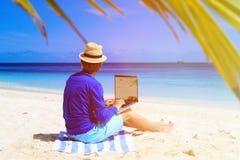 Homem novo com o portátil na praia tropical Fotos de Stock Royalty Free
