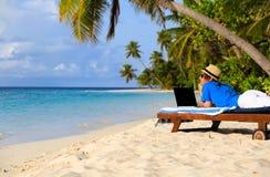 Homem novo com o portátil na praia tropical Fotografia de Stock Royalty Free