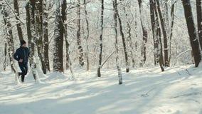 Homem novo com o relógio ou o perseguidor esperto do coração que correm na estrada coberto de neve do inverno na floresta vídeos de arquivo