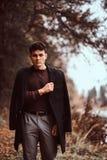 Homem novo com o revestimento que cobre seus ombros na floresta do outono foto de stock