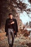 Homem novo com o revestimento que cobre seus ombros na floresta do outono imagens de stock