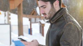 Homem novo com o smartphone na neve vídeos de arquivo