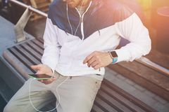 Homem novo com o telefone celular e os auriculares que sentam-se no banco fora imagem de stock