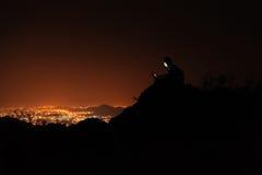 Homem novo com o telefone sobre o monte observando a opinião da cidade da noite Imagens de Stock