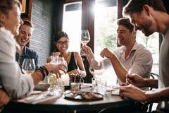 Homem novo com os amigos no restaurante fotografia de stock