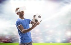 Homem novo com os auriculares da realidade virtual ou os vidros 3d sobre o campo de futebol no fundo do estádio foto de stock