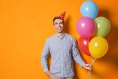 Homem novo com os balões brilhantes no fundo da cor Celebração do aniversário Imagens de Stock Royalty Free
