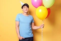 Homem novo com os balões no fundo da cor Celebração do aniversário Foto de Stock