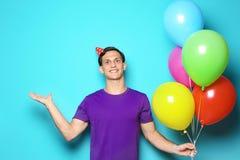 Homem novo com os balões no fundo da cor Celebração do aniversário Foto de Stock Royalty Free