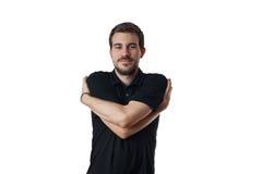 Homem novo com os braços envolvidos em torno dsi mesmo Fotografia de Stock