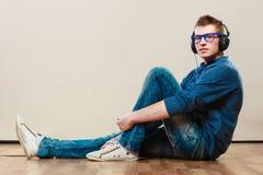 Homem novo com os fones de ouvido que sentam-se no assoalho Foto de Stock