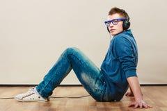 Homem novo com os fones de ouvido que sentam-se no assoalho Fotografia de Stock