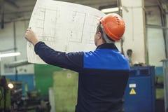 Homem novo com os modelos que trabalham em uma fábrica velha para o inst Fotografia de Stock Royalty Free