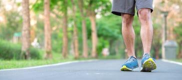 Homem novo com os tênis de corrida no parque exterior, corredor masculino do atleta pronto para movimentar-se na estrada fora, pa fotos de stock royalty free
