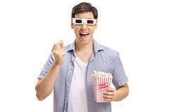 Homem novo com os vidros 3D que têm a pipoca e o riso Imagem de Stock