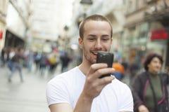 Homem novo com passeio do telefone de pilha Imagem de Stock