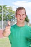 Homem novo com polegares que sorri acima Imagens de Stock Royalty Free