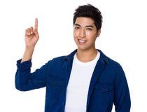 Homem novo com ponto do dedo acima Foto de Stock