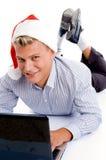 Homem novo com portátil e chapéu dos chritsmas Fotografia de Stock