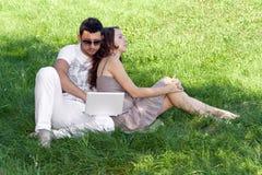 Homem novo com portátil e menina na grama verde Fotografia de Stock
