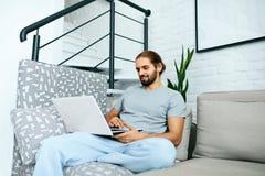 Homem novo com portátil em casa imagem de stock
