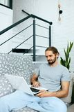 Homem novo com portátil em casa imagens de stock