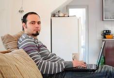Homem novo com portátil em casa Fotografia de Stock