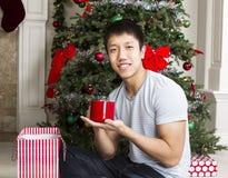 Homem novo com presente de época natalícia imagem de stock