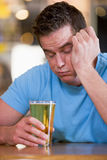 Homem novo com a queda da cerveja adormecida na barra Imagens de Stock