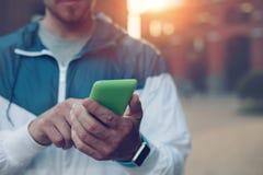 Homem novo com relógios espertos que datilografa em seu telefone celular, por do sol na rua imagem de stock royalty free
