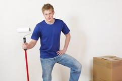 Homem novo com rolo de pintura e a caixa movente Foto de Stock Royalty Free