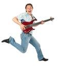Homem novo com salto da guitarra Fotos de Stock Royalty Free